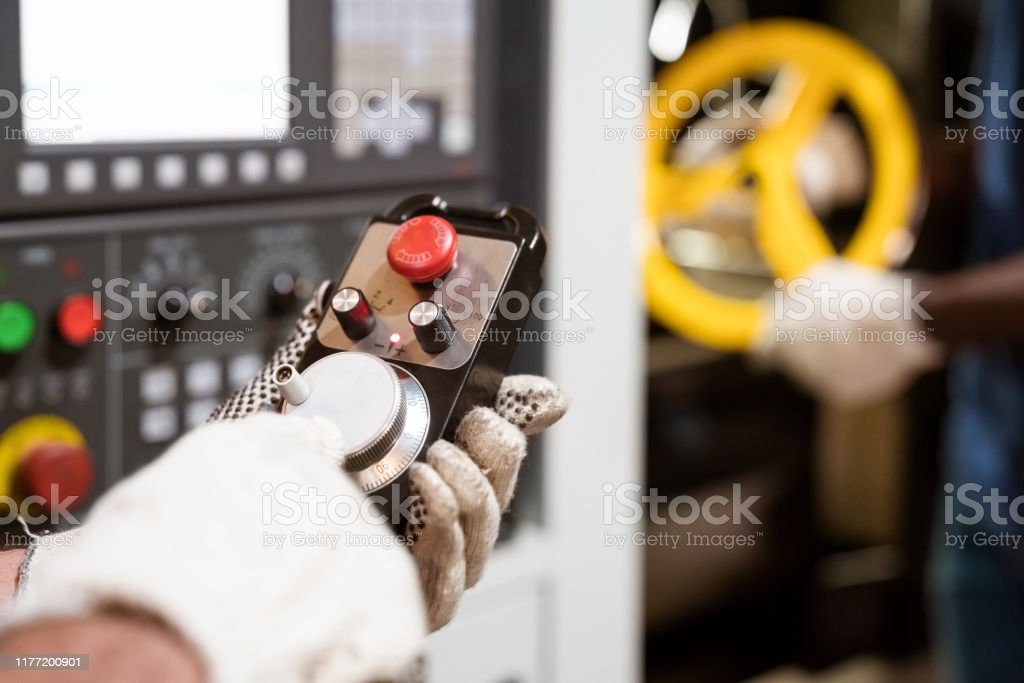 Manual worker wearing gloves using lathe machine Cropped image of manual worker turning knob. Male engineer is using lathe machinery. He is wearing protective gloves. 25-29 Years Stock Photo