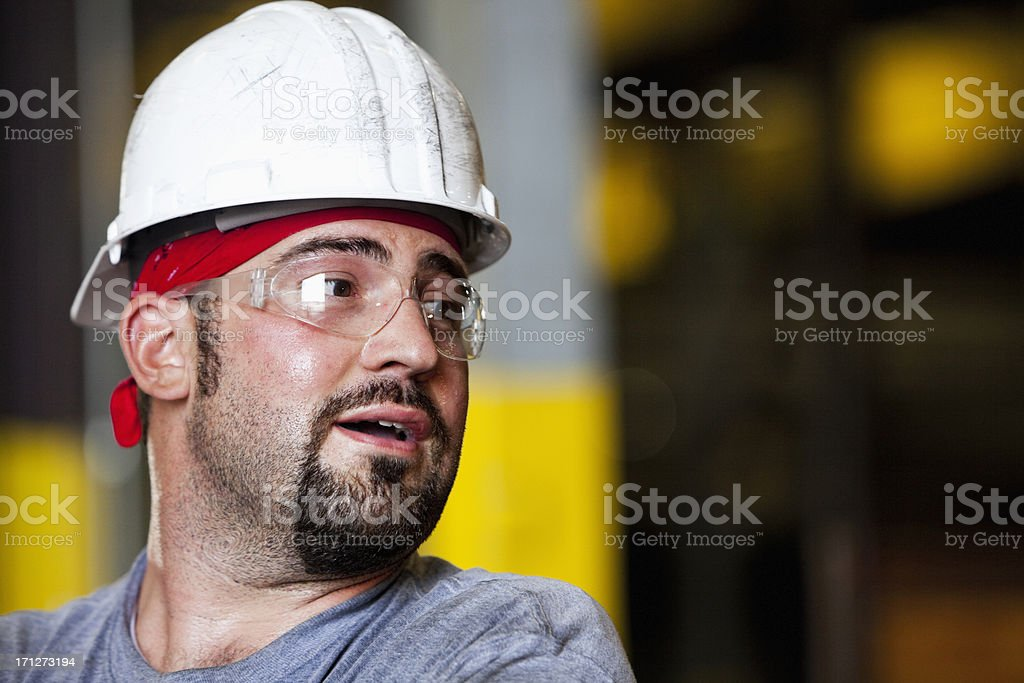 Manual worker wearing hardhat and safety glasses stock photo
