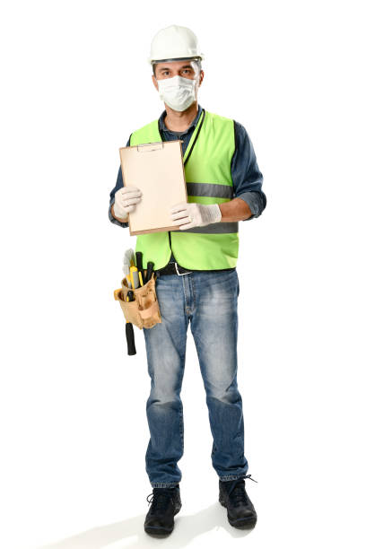 Manual worker wearing protective face mask and gloves to avoid Coronavirus epidemic holds clipboard isolated on white background. stock photo