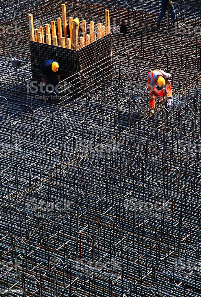 Manual worker welding concrete reinforcing steel on construction site stock photo
