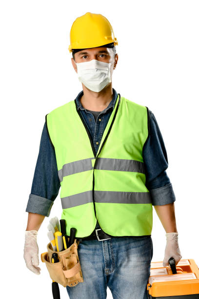 Manual worker with tool bag wearing protective face mask and gloves to avoid Coronavirus epidemic isolated on white background. stock photo