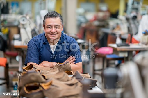 Happy Latin American manual worker working at a shoe-making factory