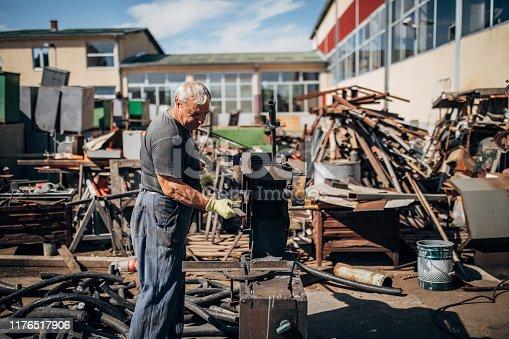 One man, mature man working on junkyard outdoors alone.