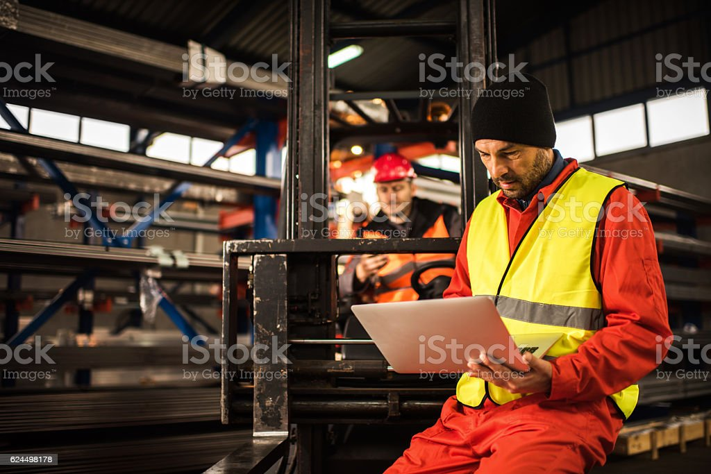 Manual worker working on a laptop in aluminum mill. stock photo
