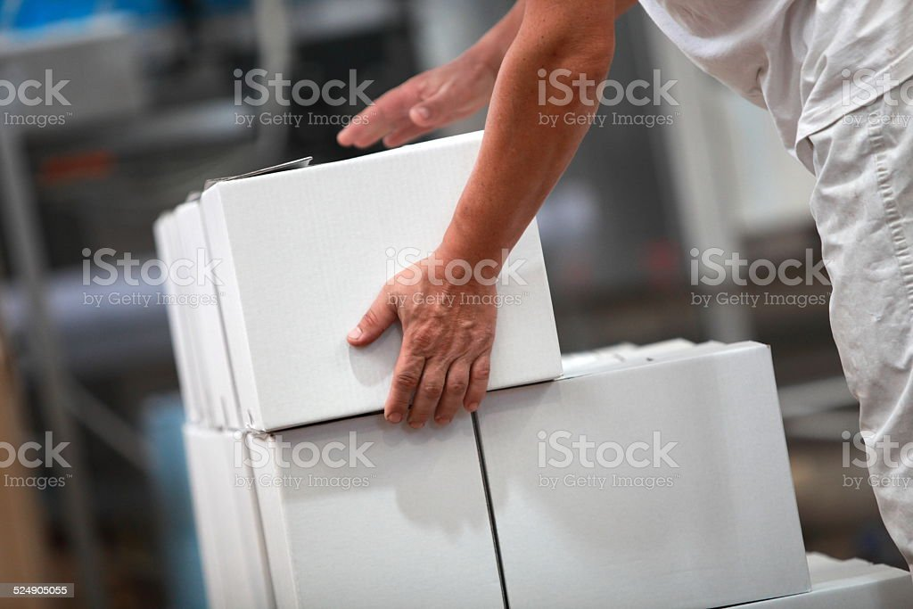 Manual worker working with boxes in factory stock photo