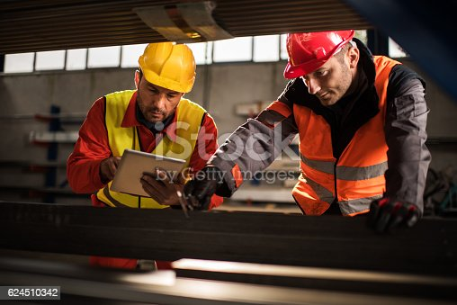 Two manual workers measuring metal in a factory, while one of them is using digital tablet. Focus is on man with yellow hardhat.