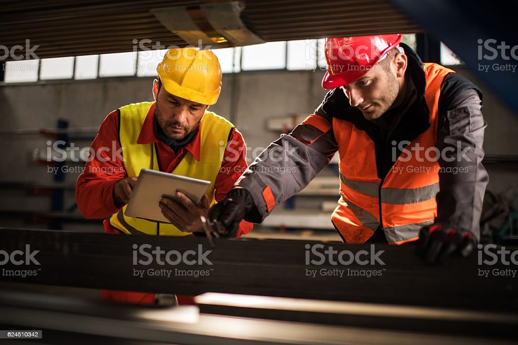 Manual workers cooperating while measuring metal in aluminum mill. stock photo