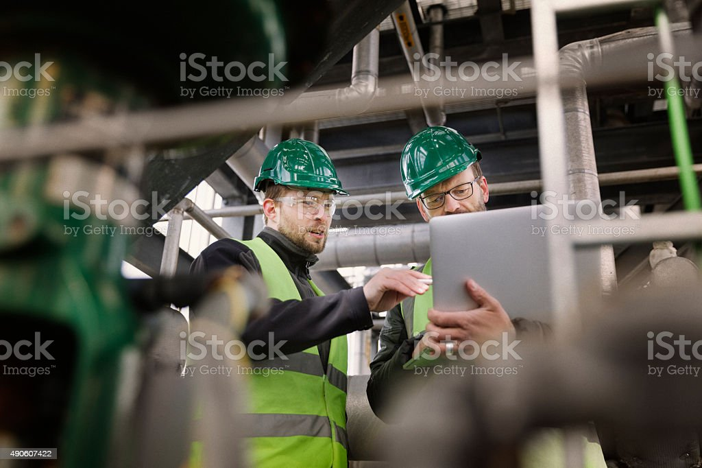 Manual workers discussing while using laptop at factory stock photo