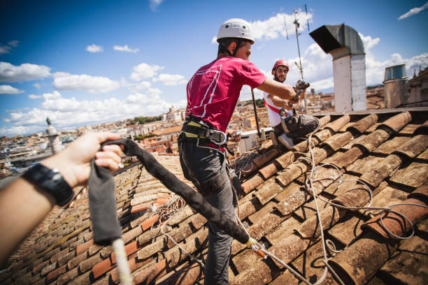 Manual workers in action on the roofs of Rome - foto stock