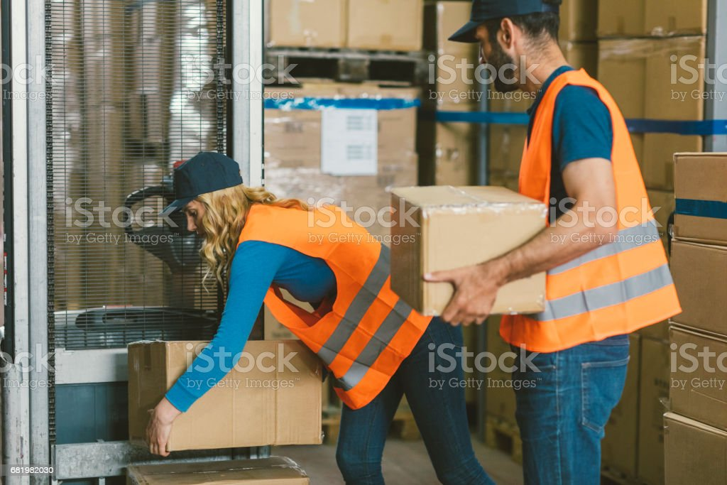 Manual workers in warehouse stacking cardboard boxes stock photo