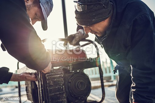 Two construction workers repairing power generator outdoors.