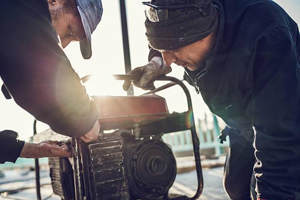 manual trabajadores reparar generador de energía. - generadores fotografías e imágenes de stock
