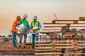 istock Manual workers talking with an architect while going through housing plans 1209265395