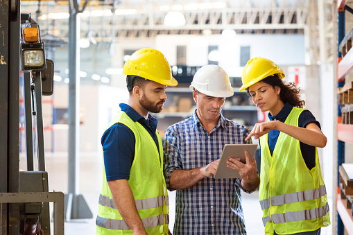 Manual Workers Using Digital Tablet In Industry Stock Photo - Download Image Now