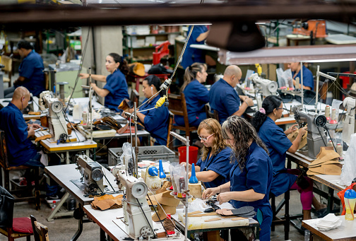 Group of Latin American manual workers working at a shoe-making factory