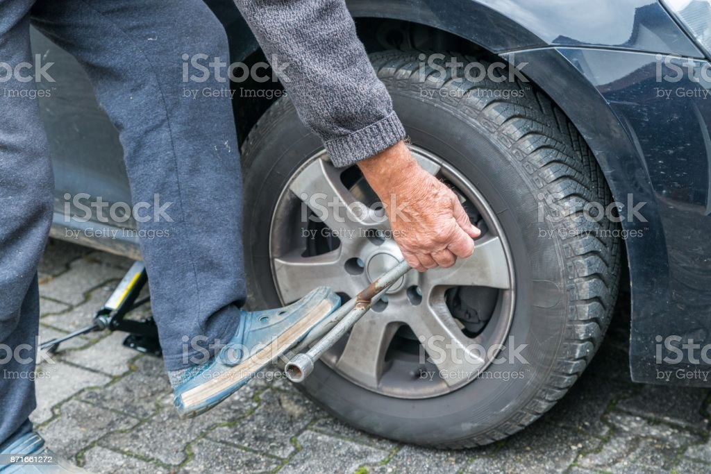 Manually tire change with four-way socket wrench stock photo
