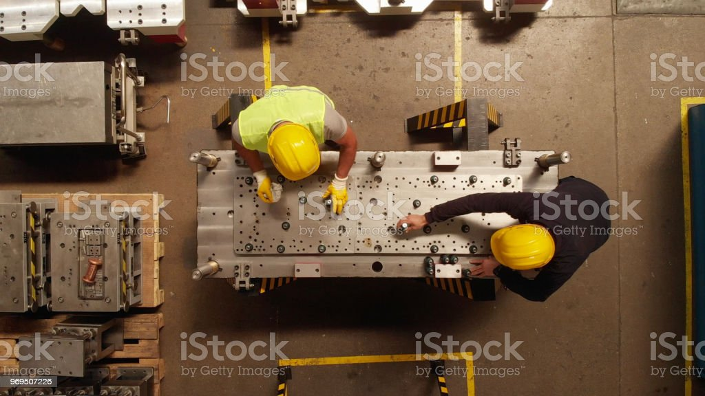 Manuel Worker in a Production Line of a Machine Part stock photo