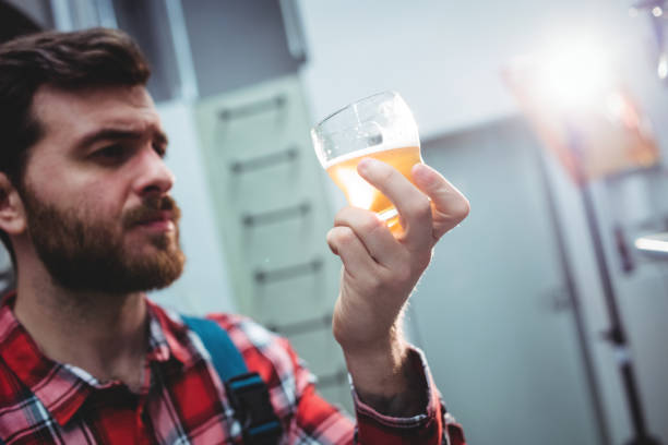 Manufacturer holding beer glass at brewery stock photo