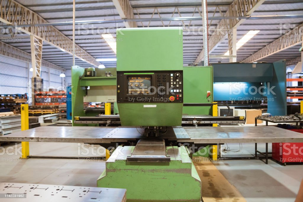 Manufacturing machinery in factory Green puller machine in industry. Manufacturing machinery in factory. Absence Stock Photo