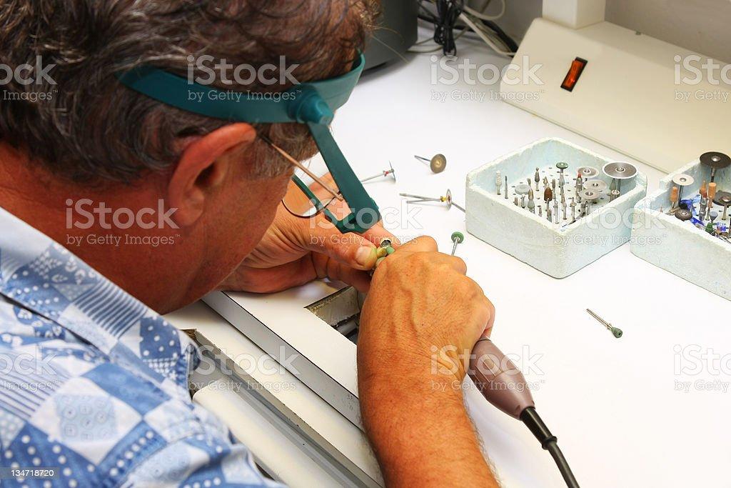 Manufacturing of dental prosthesis...senior man,dental technician at work royalty-free stock photo