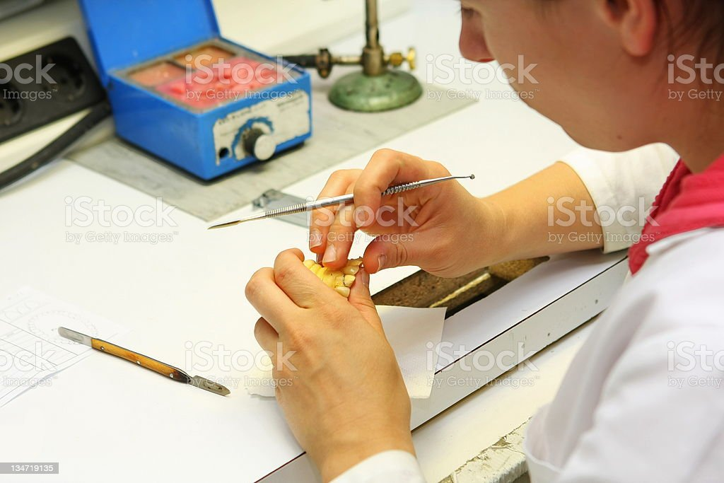 Manufacturing of dental prosthesis...young woman,dental technician at work royalty-free stock photo