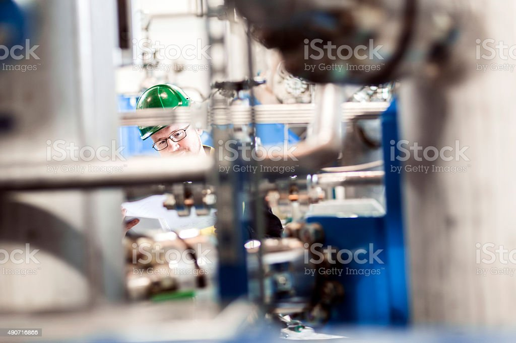 Manufacturing professional seen through machinery at factory stock photo