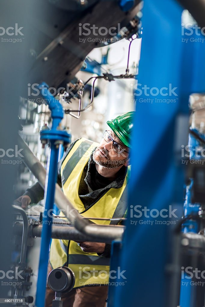 Manufacturing worker checking machines at factory stock photo