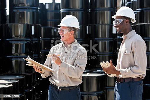 Senior man, 60s, with clipboard, taking inventory of steel barrels, with African American co-worker, 20s.