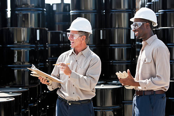Manufacturing workers by steel drums Senior man, 60s, with clipboard, taking inventory of steel barrels, with African American co-worker, 20s. toxic waste stock pictures, royalty-free photos & images