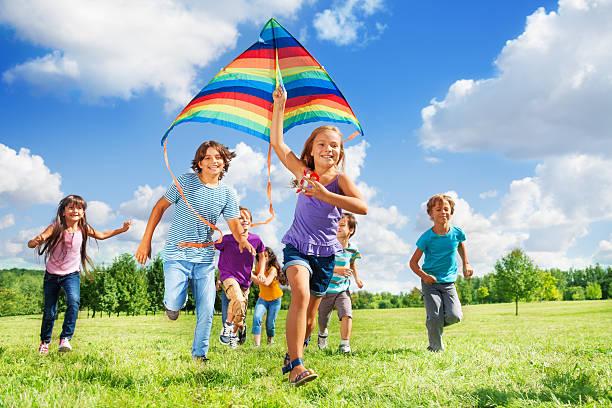Many active kids with kite stock photo