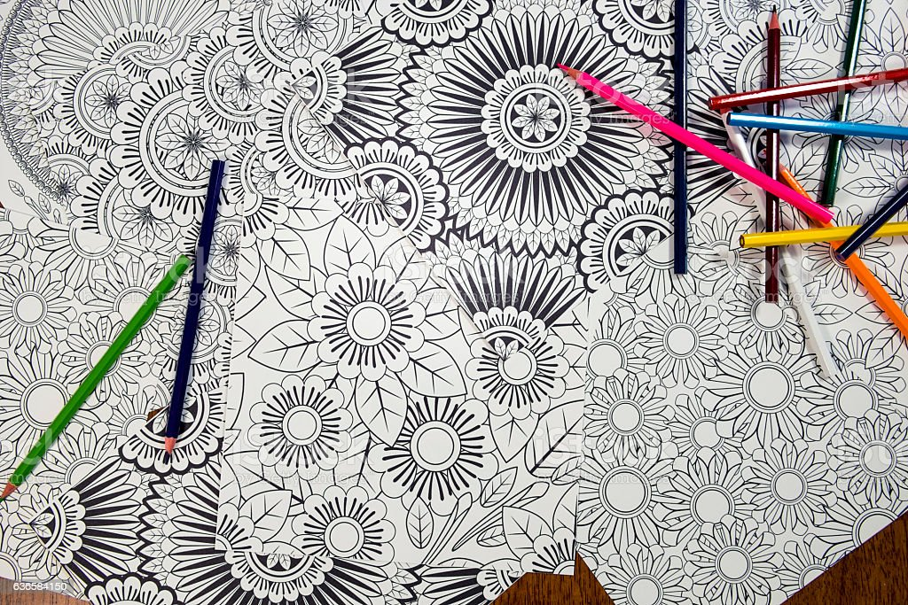 Many Adult Coloring Book Designs With Pencil Crayons stock photo