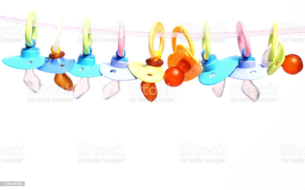 Many baby pacifiers hanging from a string stock photo