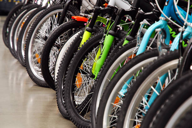 Many bicycles in sports store, seasonal sale Many bicycles in sports store parked in a row, seasonal sale shopping concept bicycle shop stock pictures, royalty-free photos & images