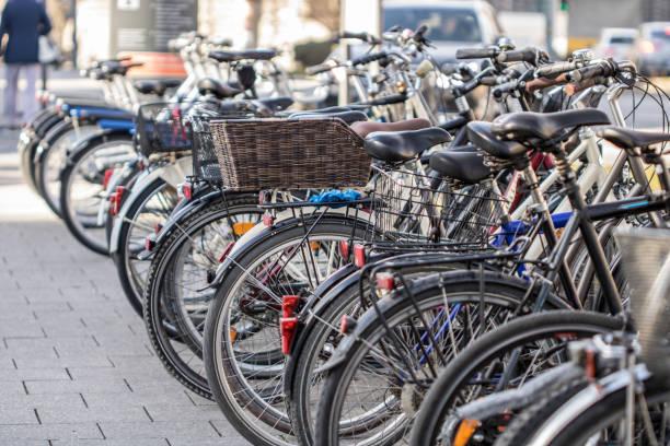 viele fahrräder auf der straße - fahrradhalter stock-fotos und bilder