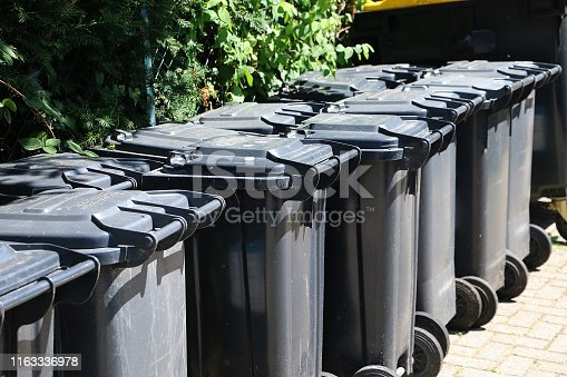 istock many black garbage cans are standing in a row 1163336978