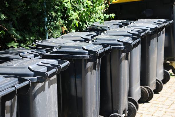 many black garbage cans are standing in a row stock photo
