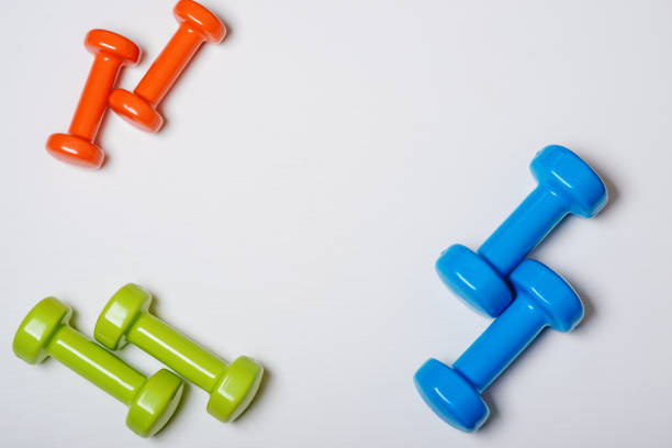 many blue green and one orange in the middle dumbbells on a white background ,concept preparing to fitness sports equipment top view mock up stock photo