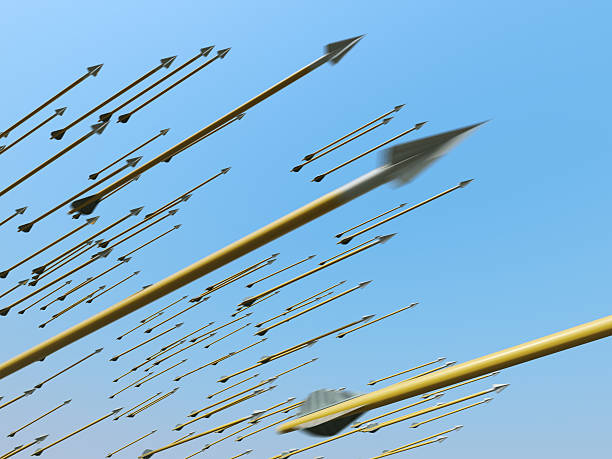 Many blurred arrows in motion flying through clear blue sky stock photo