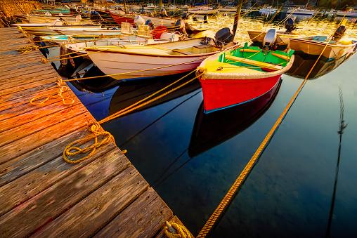 Many boats tied up at dock at sunrise
