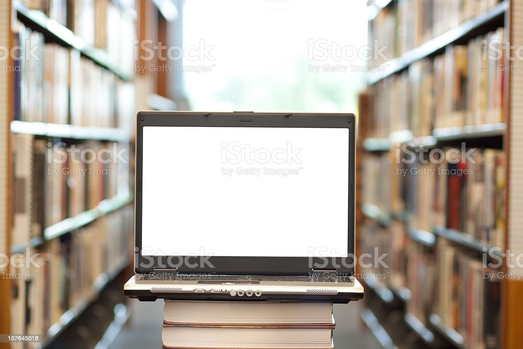 Many books and laptop in library - horizontal stock photo