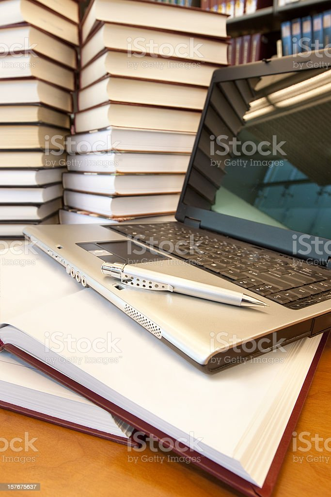 Many books and laptop in library - vertical stock photo