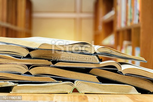 istock Many books are opened overlapping. Put on the table in the library. 1011190130