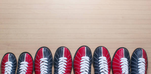 Many bowling shoes on floor. Entertainment for groups of friends. Copy space. Top view stock photo