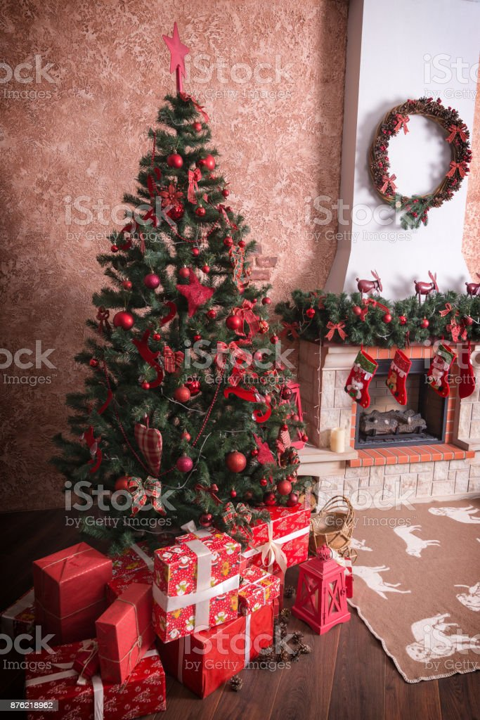 Many boxes with Christmas presents under the Christmas tree near the fireplace. stock photo