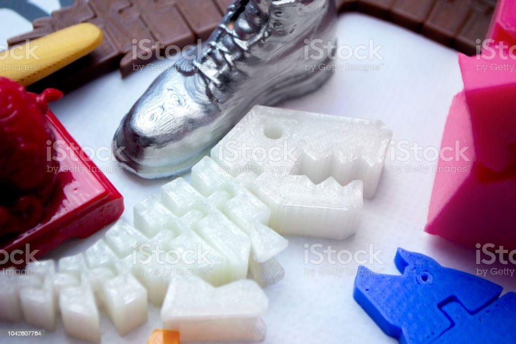 Muchos objetos multicolores brillantes impresos en Impresora 3d se encuentran sobre una superficie plana - foto de stock