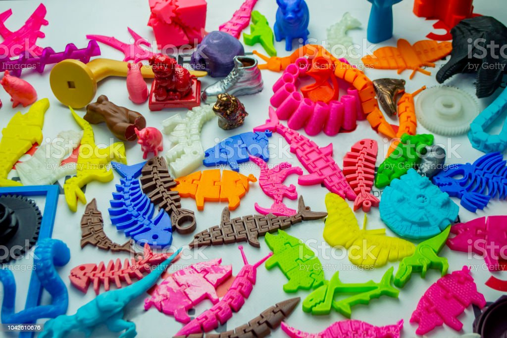 Many bright multi-colored objects printed on 3d printer lie on flat surface stock photo