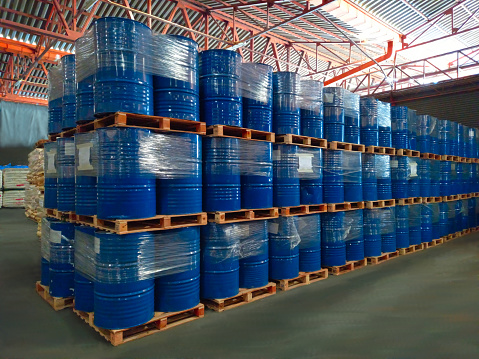 Many blue buckets are stacked on top of each other. In warehouse