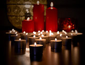 Holiday table with three red candles in vintage brass candelabras. Candlelight flames of cylindrical wax candles. Burning candlesticks on blurred background of table setting with fresh fruits