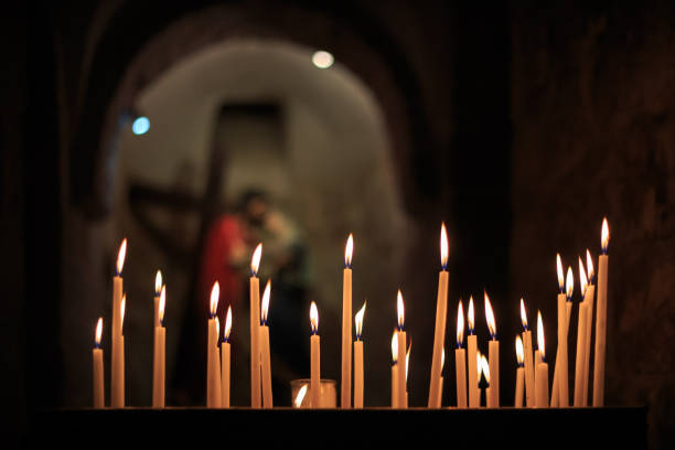 Many candles burn in the church stock photo