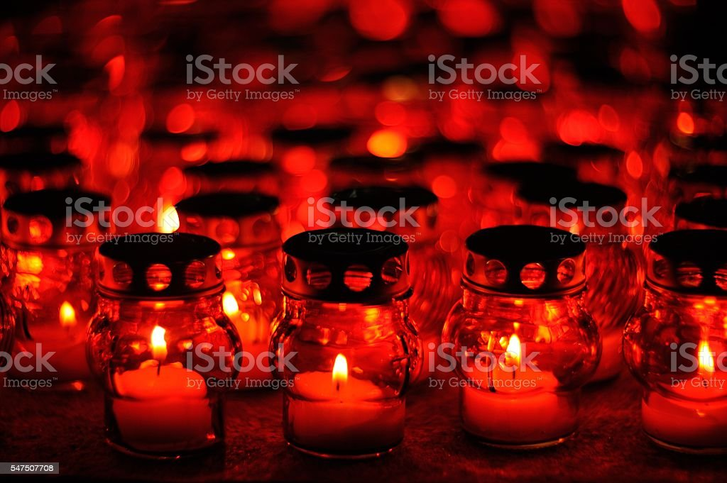 Many candles burning in red candle holders at night stock photo